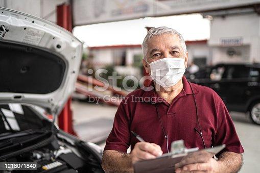 Portrait of auto mechanic senior man with face mask at auto repair shop