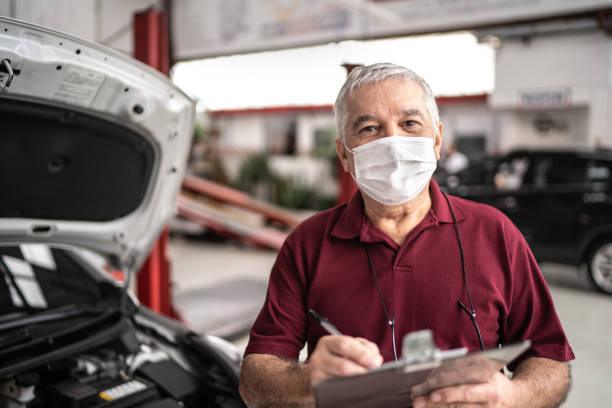 Portrait of auto mechanic senior man with face mask at auto repair shop stock photo