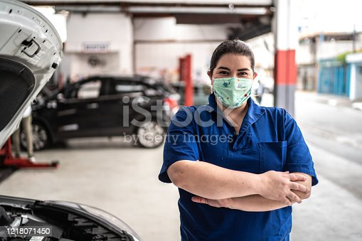 istock Portrait of auto mechanic woman with face mask at auto repair shop 1218071450