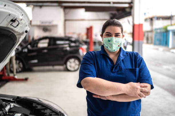 portrait of auto mechanic woman with face mask at auto repair shop - servizi essenziali foto e immagini stock