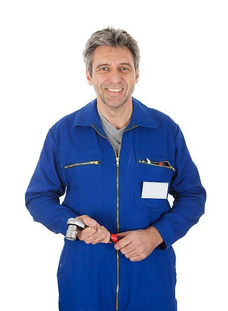 porträt von automechanic hält ein schraubenschlüssel - jumpsuit blau stock-fotos und bilder