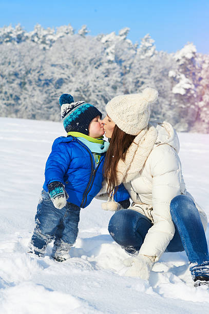 Portrait of baby boy and mother in winter day stock photo