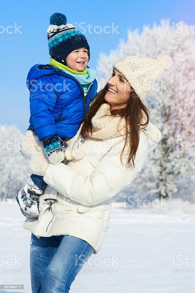 Portrait of baby boy and mother in winter day Happy smiling family in snowy day - winter portrait of mother and baby boy 2015 Stock Photo