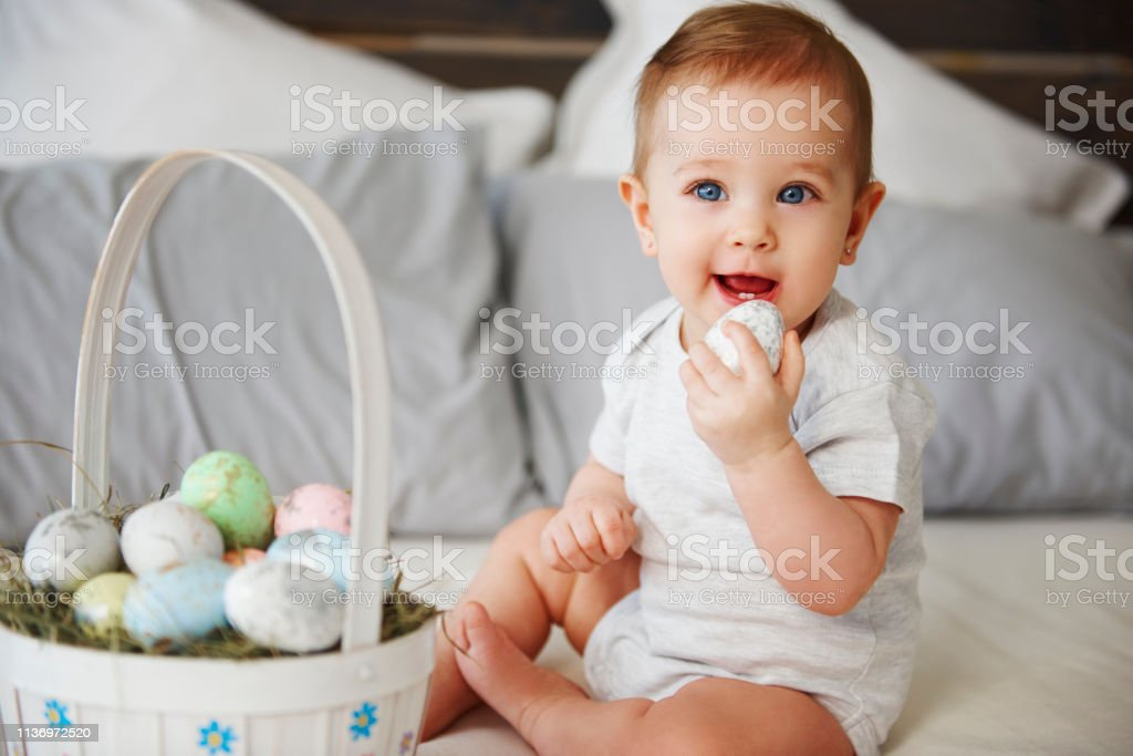 Portrait of baby eating easter egg in bed stock photo