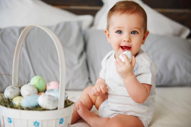 Porträt des Babys essen Osterei im Bett – Foto