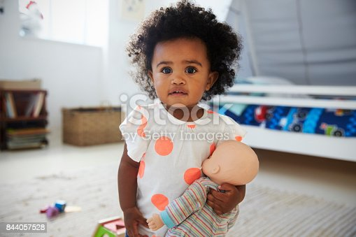 istock Portrait Of Baby Girl Playing With Doll In Playroom 844057528