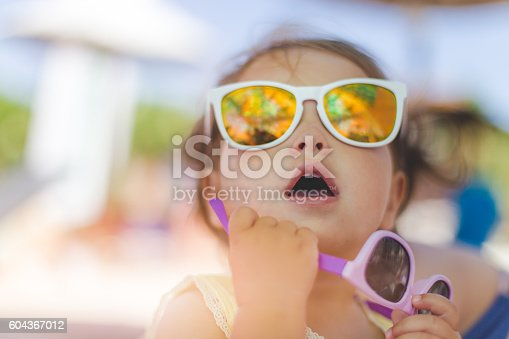 604367022 istock photo portrait of baby girl with sunglasses on a beach 604367012