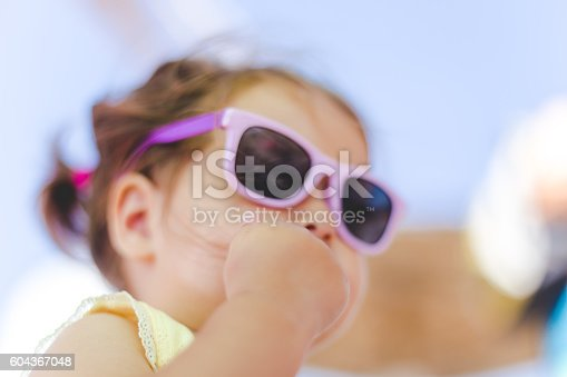 istock portrait of baby girl with sunglasses on a beach 604367048