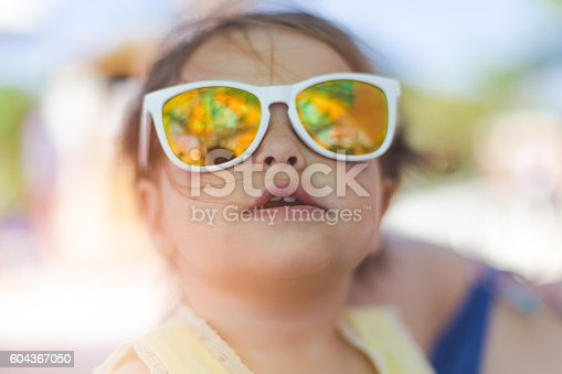 604367022 istock photo portrait of baby girl with sunglasses on a beach 604367050