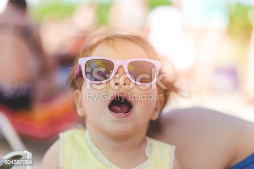 604367022 istock photo portrait of baby girl with sunglasses on a beach 604367054