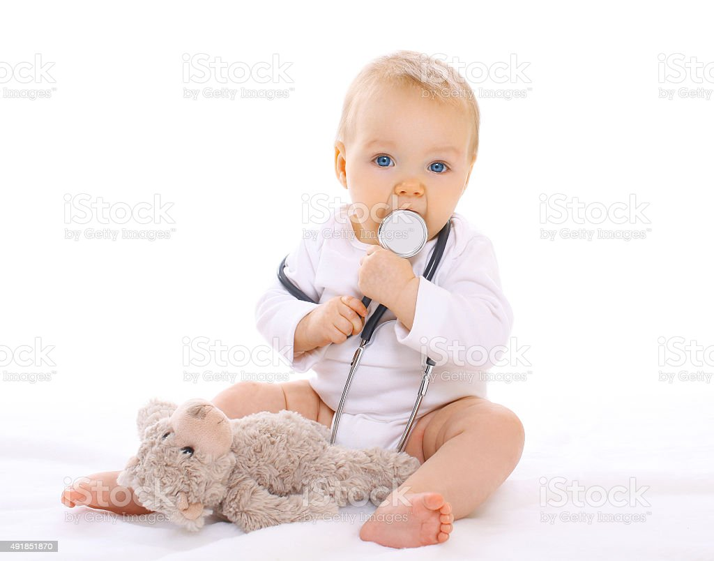 Portrait of baby playing with stethoscope and teddy bear stock photo