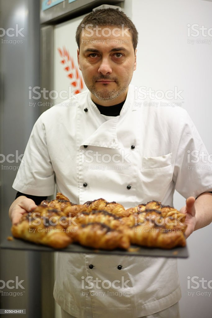 Portrait of baker holdng croissants tray stock photo