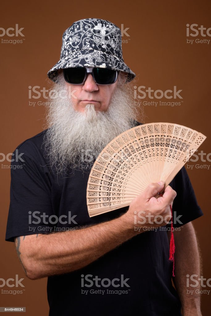 Portrait of bald man with long gray beard holding hand fan stock photo