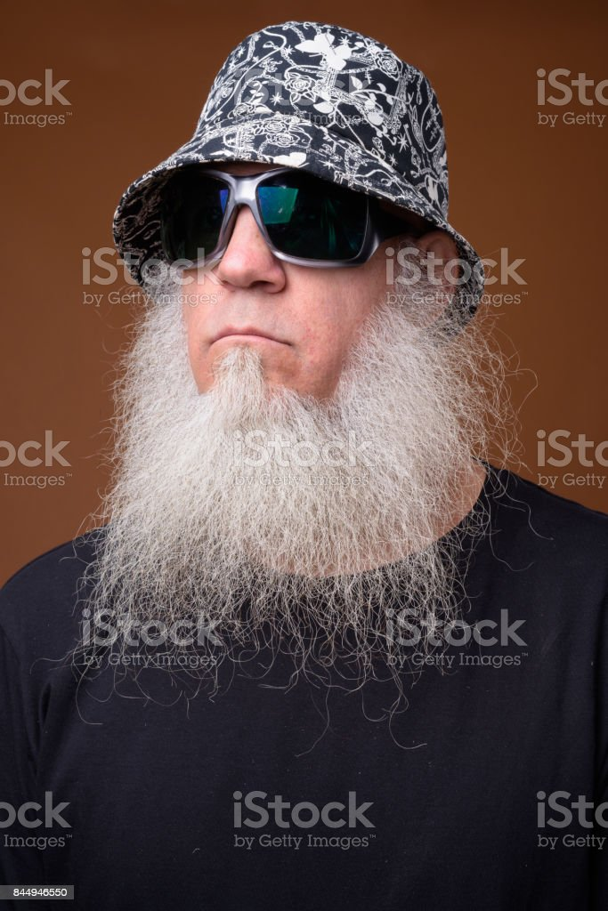 Portrait of bald man with long gray beard wearing bucket hat and sunglasses stock photo
