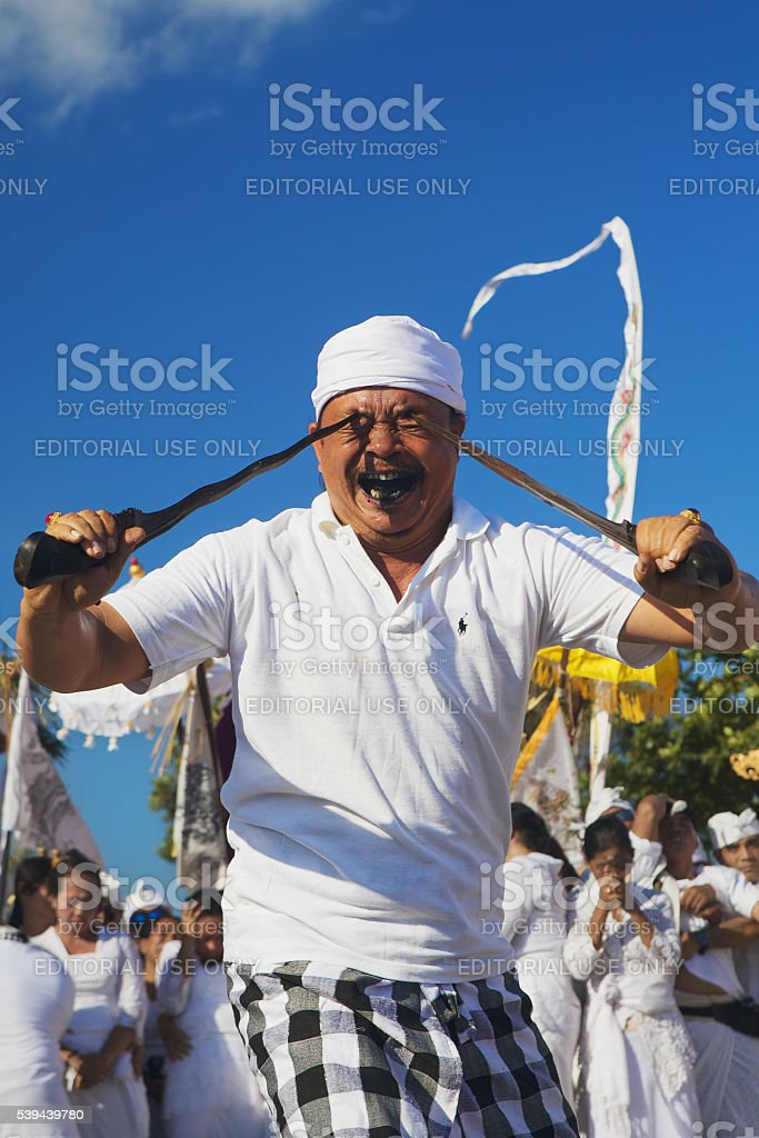 Portrait of Balinese man in trance with traditional daggers stock photo
