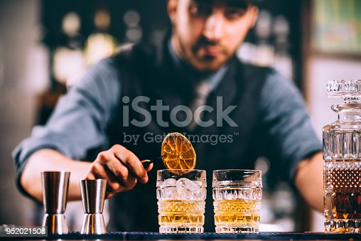 Portrait of barman adding ingredients and creating cocktail drinks on bar counter