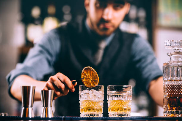 portrait of barman adding ingredients and creating cocktail drinks on bar counter - bartender стоковые фото и изображения