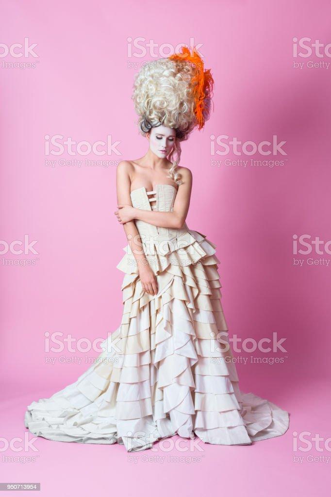 Portrait of Baroque Woman wearing wig, pink backgroud stock photo