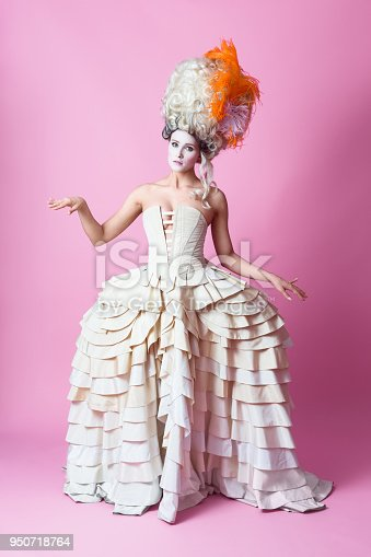 Portrait of beautiful woman wearing a big wig and   dress in baroque style. Standing against pink background.