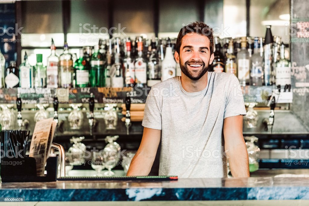 Portrait of bartender standing at bar counter stock photo