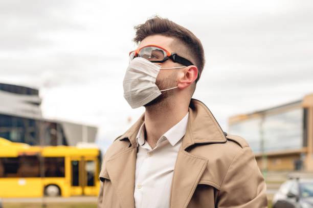 Porträt eines bärtigen kaukasischen Mannes in beigeer Jacke und weißem Hemd in der Stadt. Geschäftskonzept. Kaukasier Kerl mit Schutzbrille, die Gesichtsmaske verwenden – Foto