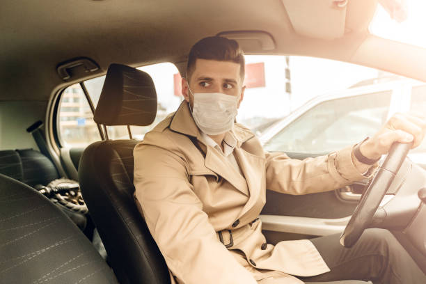 portrait of bearded fashion man in beige jacket and white shirt in the urban city. business concept. handsome adult human with face mask drives a car - businessman covid mask foto e immagini stock