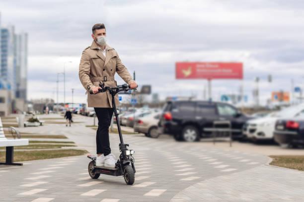 Porträt eines bärtigen Modemannes in lässiger Jacke und weißem Hemd im Freien auf der Straße. Lifestyle-Konzept mit Kopierraum. Schöne junge Mensch mit Gesichtsmaske auf neuen Elektro-Kick-Scooter – Foto