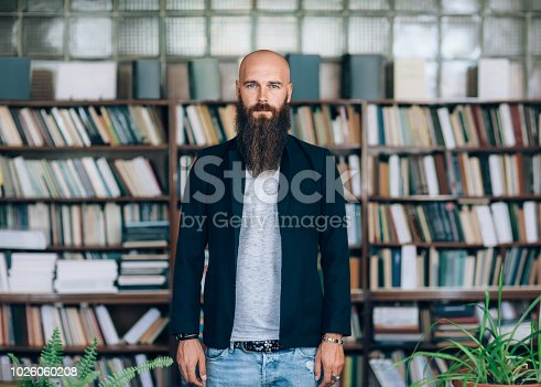 istock Portrait of bearded hipster man in library 1026060208