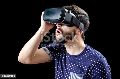 istock Portrait of bearded male with virtual reality glasses on his head isolated on black background 686259886