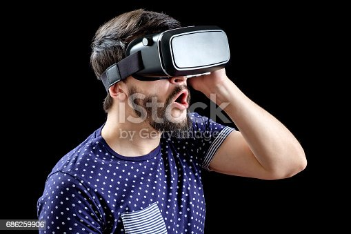 istock Portrait of bearded male with virtual reality glasses on his head isolated on black background 686259906