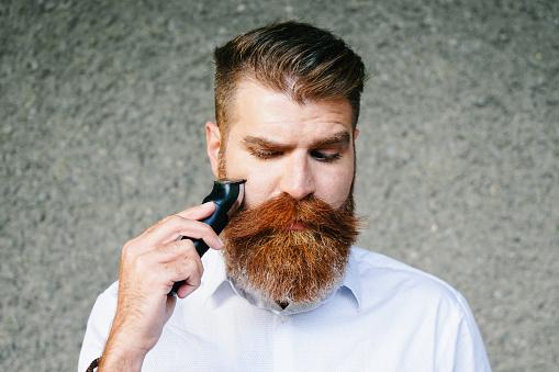 Portrait of bearded man trimming his beard.