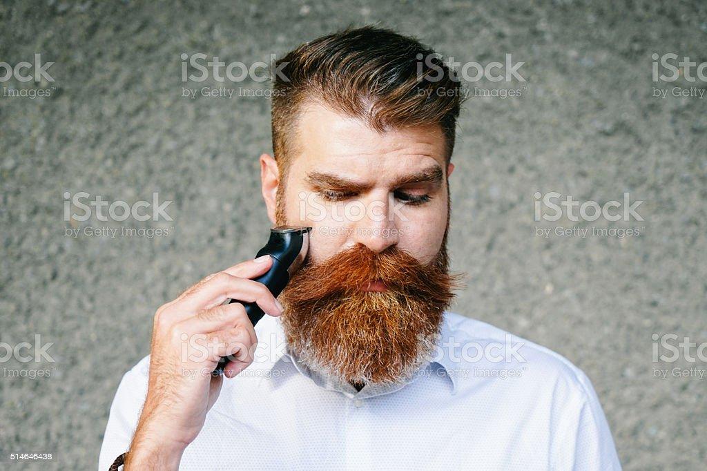 Retrato de hombre con barba corte su barba - foto de stock