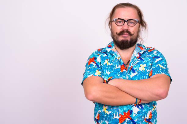 Portrait of bearded man with mustache and long hair against white background wearing Hawaiian shirt stock photo