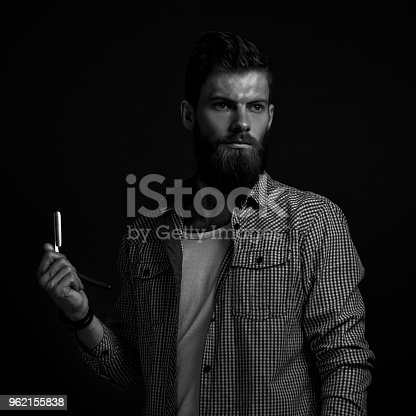 542972720 istock photo Portrait of bearded man with straight razor 962155838