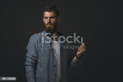 542972720 istock photo Portrait of bearded man with straight razor 962155890