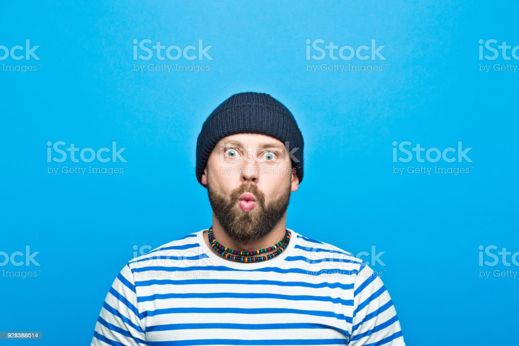 Portrait of bearded sailor whistling against ble background Portrait of bearded man wearing striped t-shirt and beanie hat whistling at camera. Studio shot, blue background. 30-34 Years Stock Photo