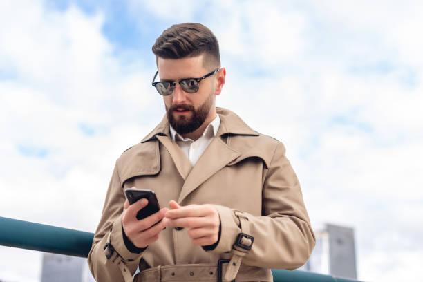 Porträt eines bärtigen ernsten Mannes in beige Jacke und weißem Hemd in der Stadt. Geschäftskonzept. Schöne Person mit modernen Handy im Freien – Foto