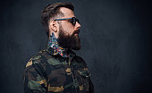 Portrait of bearded tattooed hipster male dressed in a military jacket over grey background.