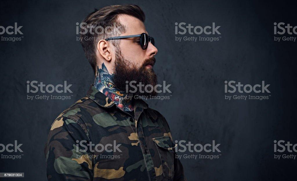 Retrato de hippie tatuado barbudo macho vestida com uma jaqueta militar. - foto de acervo