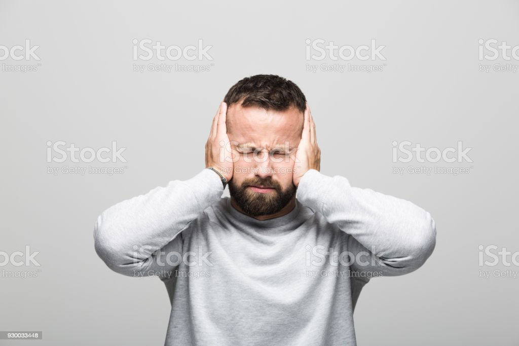 Portrait of bearded young man suffering headache Portrait of bearded young man suffering headache, holding hands on ears. Studio shot, grey background. 30-34 Years Stock Photo