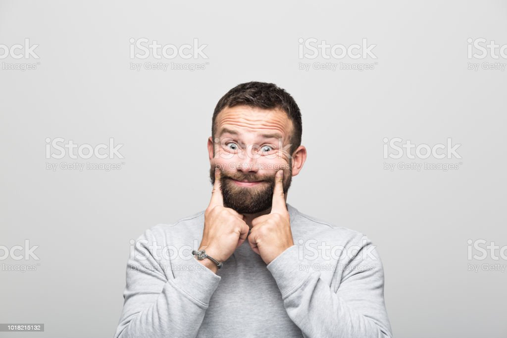 Portrait of bearded young man with fake smile, grey background Bearded young man looking at camera and making fake smile with index fingers. Studio shot, grey background. 30-34 Years Stock Photo