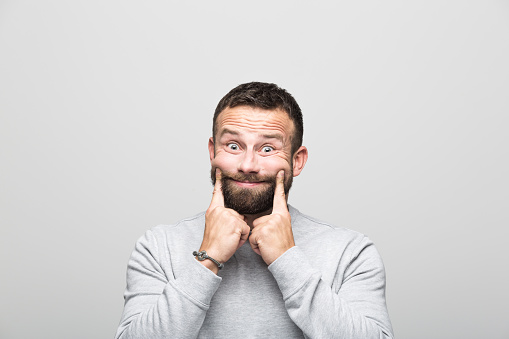 Portrait Of Bearded Young Man With Fake Smile Grey Background Stock Photo - Download Image Now