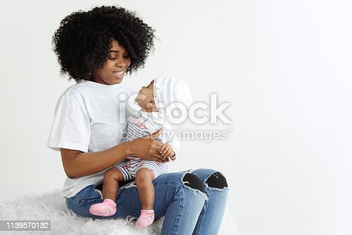 1074272738 istock photo Portrait of beautiful african woman holding on hands her little baby 1139570132