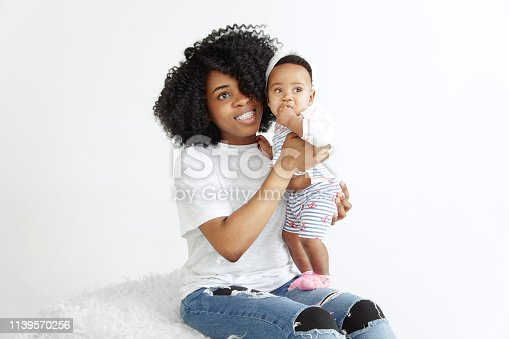 1074272738 istock photo Portrait of beautiful african woman holding on hands her little baby 1139570256