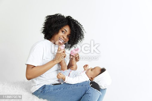 1074272738 istock photo Portrait of beautiful african woman holding on hands her little baby 1139570276