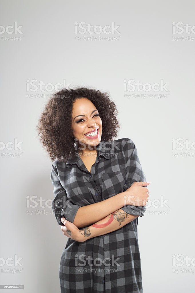 Portrait of beautiful afro american young woman Portrait of beautiful afro american young woman wearing casual checkered dress, standing against grey background and laughing at camera. Adult Stock Photo