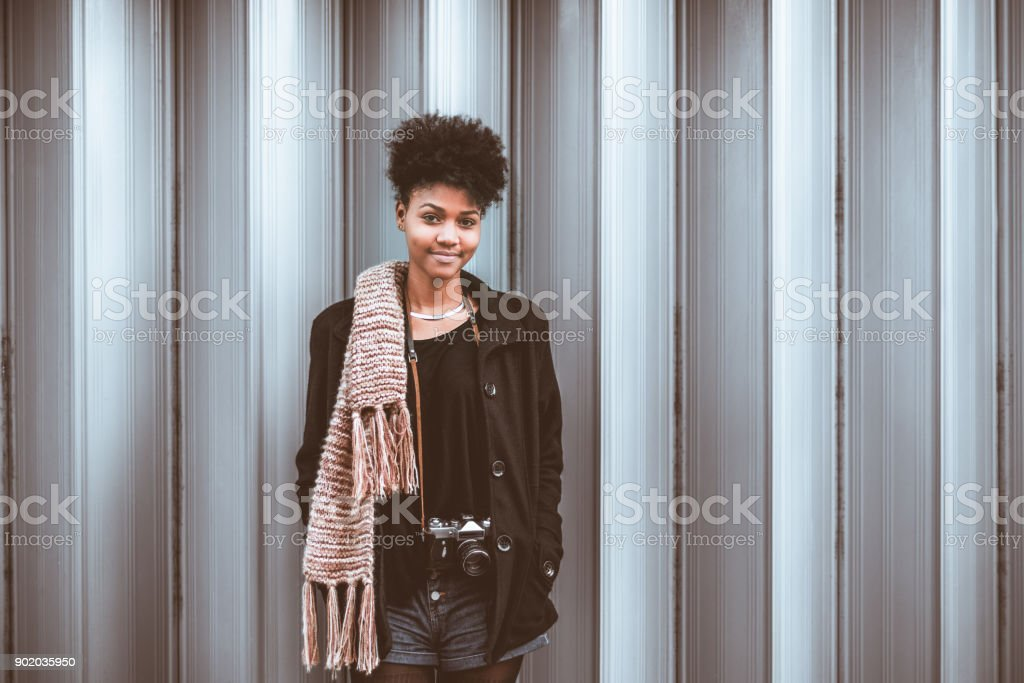 Portrait of beautiful Afro tourist female with vintage camera stock photo