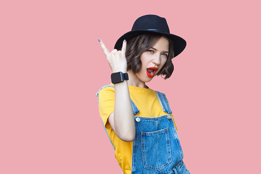 Portrait of beautiful amazed young woman in yellow t-shirt, blue denim overalls with makeup and black hat standing with rock horns, screaming and looking at camera. studio shot on pink background.