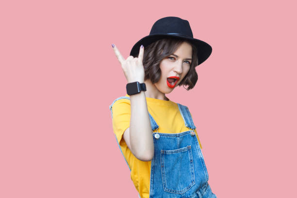 portrait of beautiful amazed young woman in yellow t-shirt, blue denim overalls with makeup and black hat standing with rock horns, screaming and looking at camera - rock musician stock pictures, royalty-free photos & images