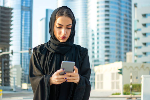 Portrait of beautiful Arab businesswoman wearing hijab using cell phone on the street with the skyscrapers in the background stock photo